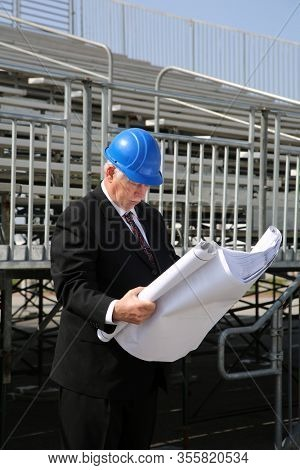 Contractor. Contractor examining blueprints at a construction site. Construction Site Supervisor or Contractor with Blue Prints at a work site. Building and Homes being built world wide. United States