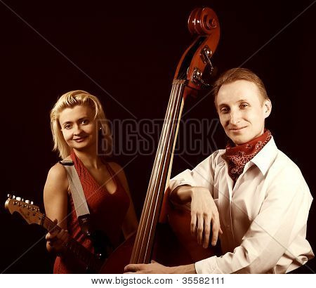 Musicians with contrabass and guitar. Over black background.