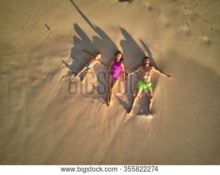Family lying down on beach aerial top view drone shot at Seychelles, Mahe