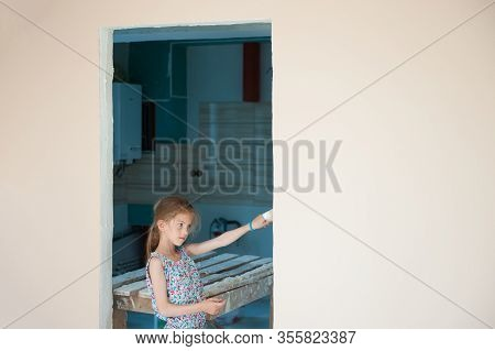 Home Reconstruction Concept Of Beautiful Little Girl Painter With Paint Brush In Hand In House Room