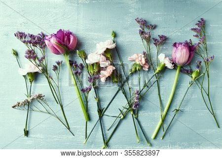 An arrangement of spring flowers on painted wooden background. Flat lay