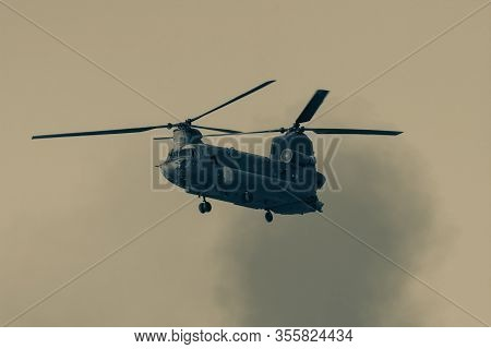 Military Combat And War With Chinook Helicopter Flying Through The Chaos And Destruction. Smoke And