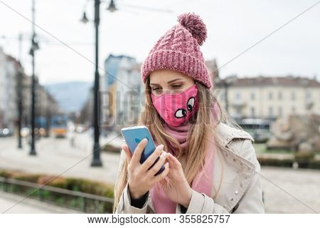 Anxious woman wearing corona mask checking news on her phone in lockdown city