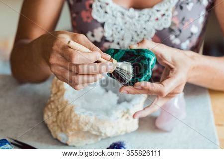 Young woman dusting a malachite with a brush