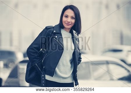 Happy young fashion woman with handbag on city street Stylish female model in black leather jacket and light gray pullover