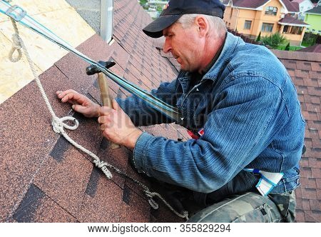 Kyiv, Ukraine - March, 17, 2020: Asphalt Roofing Contractor Laying Asphalt Shingles On House Rooftop