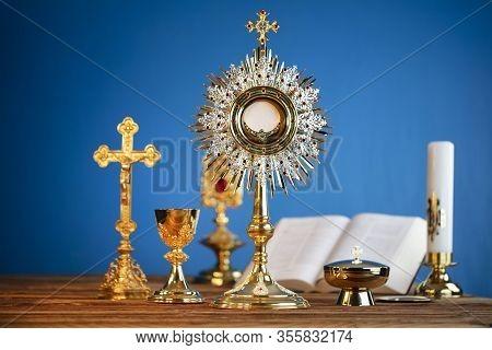 Catholic Religion Concept. Catholic Symbols Composition. The Cross, Monstrance,  Holy Bible And Gold