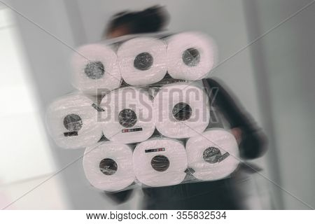 Coronavirus shopping frenzy at store woman carrying many packages of toilet paper in panic buying afraid of shortage in store. Motion blur.