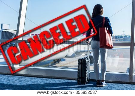 Plane business travel and flight canceled because of coronavirus travel ban. Crisis in aviation, airline and industry due to corona virus covid-19 or other. Canceled red stamp text on plane in airport