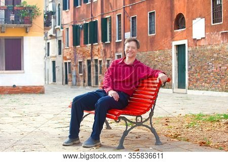 Handsome Smiling Caucasian Male Wearing Red Dress Shirt In Early Fifties Sitting On Red Painted Benc
