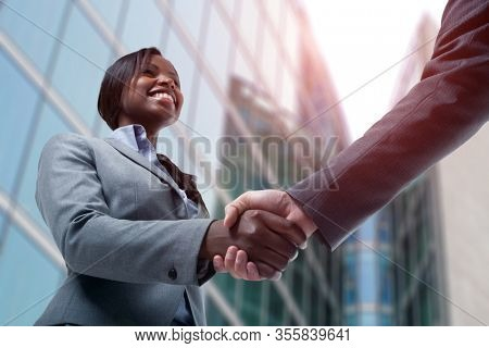 Smiling young black business woman shaking hands with a white business man