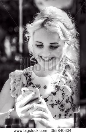 A Young, Sympathetic, Blonde Woman Using A Smartphone, Black And White Portrait Of A Woman Through A