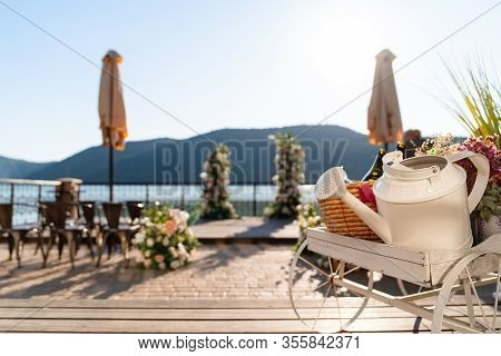 White Pushcart With A Watering Can For Irrigation On The Background Of A Wedding Arch On Lake Abrau