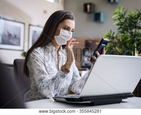 Young woman wering mask. Home office