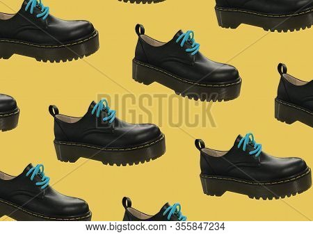 Black Leather Platform Shoes Isolated On Yellow Background. Classic Shoes On A High Black Tractor Pl
