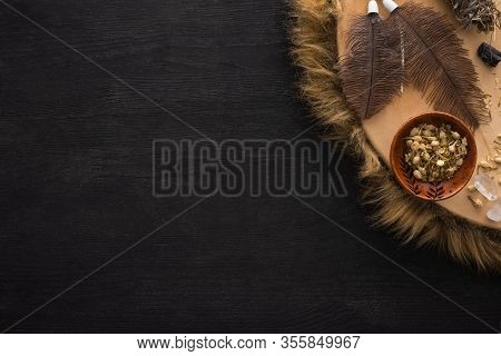 Top View Of Shamanic Tambourine With Feathers, Dry Flowers And Crystals On Black Wooden Background