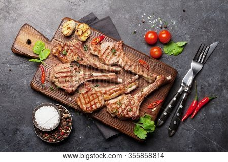 Grilled lamb ribs on cutting board. Hot rack of lamb with spices and condiments. Top view on stone table