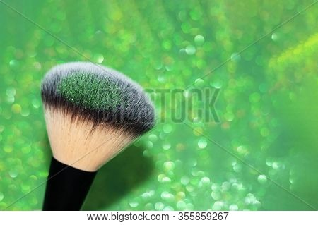 Black Powder Brush With Green Shimmer Shadows For St.patricks Day Makeup On A Green Glitters Backgro