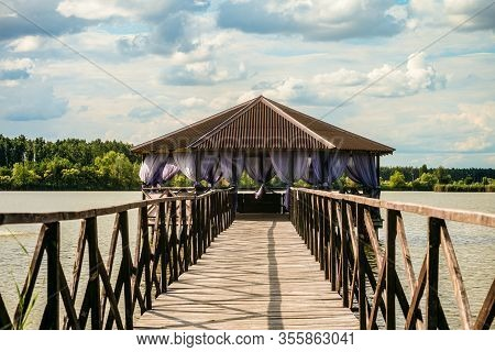 Wooden Gazebo On The Quet Lake. Cloudy Scape With Over Water Architecture. Distance Perspective.