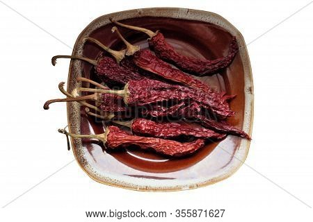 Dried Red Pepper Lies On A Brown Plate. Isolated. White Background.