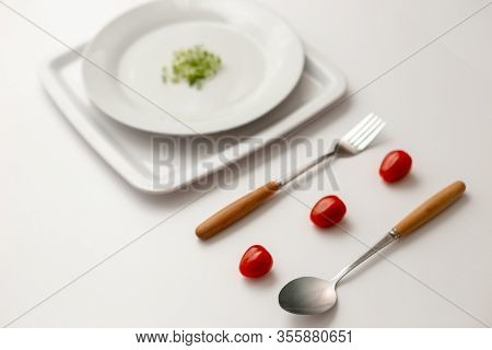 Three Red Cherry Tomatoes Between A Fork And A Spoon, Small Bunch Of Green Watercress On A Round Whi