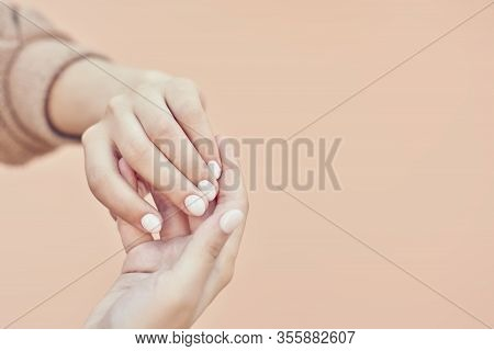 An Unrecognizable Woman Arms. Woman Showing Hands With Beautiful Light Manicure On Nails. Stylish Tr
