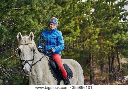Young Woman Rider In A Blue Blazer And Sporting A Cap For A Walk On A White Horse On A Cloudy Winter