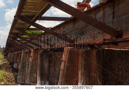 Rusting Low Train Trestle With Outrigger Walkway Outside A  Derelict Manufacturing Facility, Horizon