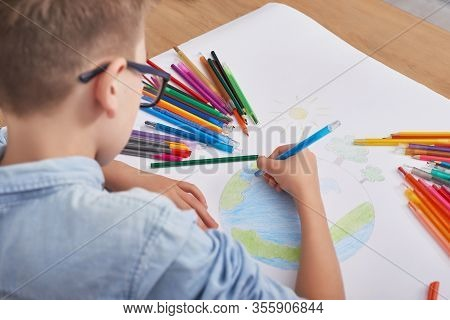 Child Boy Draws Planet For Earth Day. Protection Of Enviroment, Mother Earth Day Greeting And Celebr