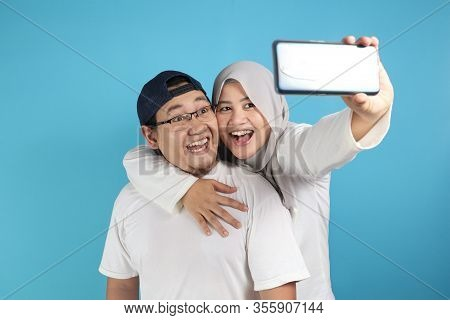 Portait Of Happy Asian Muslim Couple Making Selfie And Smiling, Husband And Wife Hugging Full Of Lov
