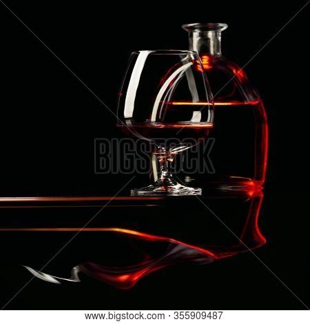 Snifter And Bottle Of Brandy On A Black Background. Copy Space.