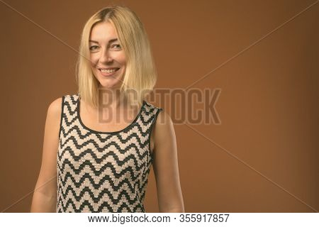 Beautiful Businesswoman With Short Blond Hair Against Brown Background