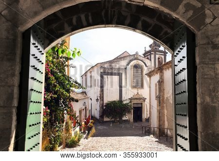 View through the old gate on cathedral and houses in medieval narrow street, Obidos, Portugal, Europe