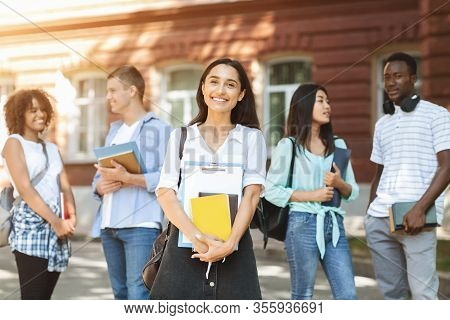 New Student. Portrait Of Happy Arabic Girl With Notepads Posing Outdoors In University Campus With H