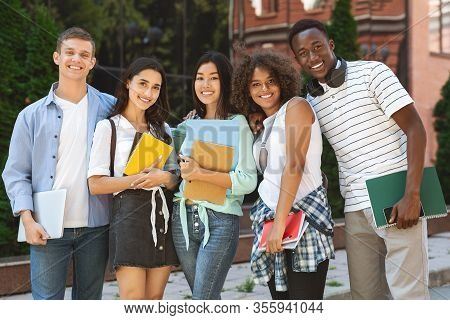 Group Portrait Of Multicultural College Students Posing In Campus With Workbooks In Hands
