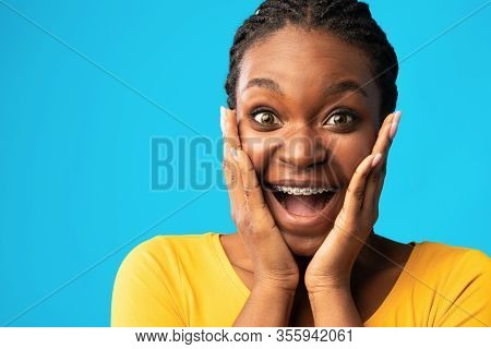 Omg. Excited Black Lady Screaming In Excitement Touching Face Looking At Camera Posing Over Blue Stu