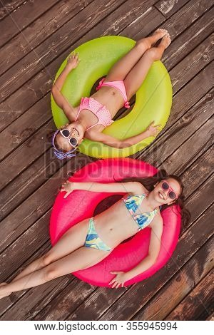From Above Cheerful Friends In Vivid Sunglasses And Colorful Swimwear Smiling At Camera, While Layin