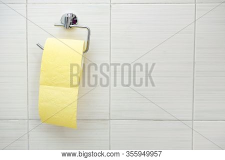 A Roll Of Yellow Toilet Paper Hanging On A Wall Fixture In A Rest Room, Copy Space.