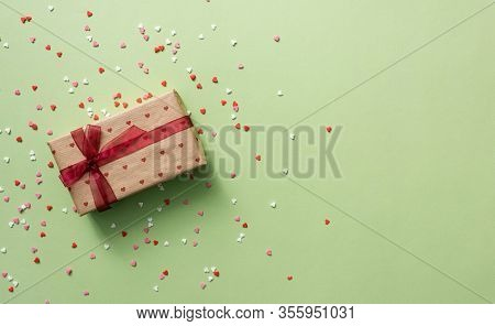 Gift box with red tied bow, among tiny heart shapes. Top view holiday background.