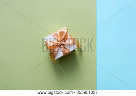 Gift box with golden tied bow, on two-color background. Top view holiday background.