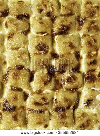 Roasted Gnocchi In Cheese Sauce, Above View. Close-up On Cheese Gnocchi Tray. Italian Traditional Fo