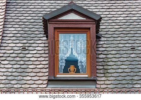 Dark Old Wooden Window With Beautiful Vase. Tiled Roof. Architecture And Travel In Germany.