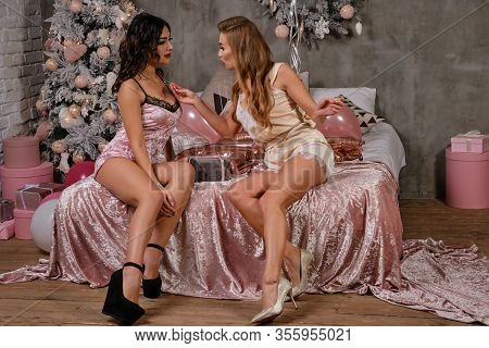 Two Beautiful Women In Sexy Lingerie Having Fun During Hen-party, Sitting On Bed, Boasting Jewelry.