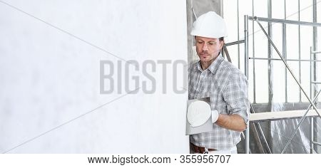 Plasterer Man At Work With Trowel Plastering The Wall Of Interior Construction Site Wear Helmet And