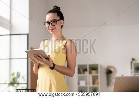 Pretty young brunette businesswoman in eyeglasses and dress using touchpad in front of camera in office environment
