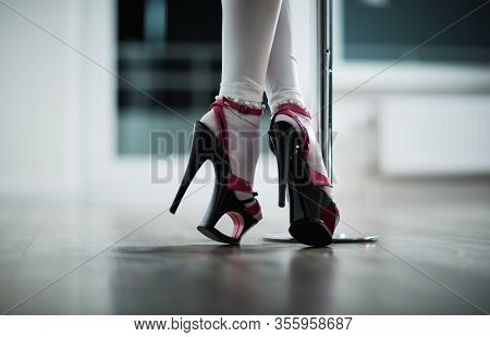 The Legs Of A Dancer On A Pylon In Striptease Shoes. Dance Photo