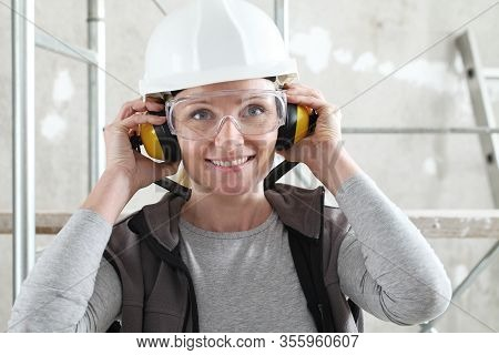 Smiling Woman Worker Portrait Wearing Helmet, Safety Glasses And Hearing Protection Headphones, Scaf
