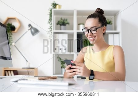 Happy young elegant businesswoman with toothy smile scrolling in smartphone while enjoying break by workplace