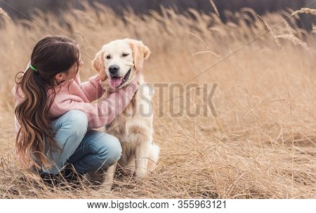 Happy girl petting young dog in high dry grass