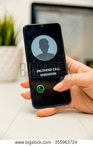 Unknown Caller. A Man Holds A Phone In His Hand And Thinks To End The Call. Incoming From An Unknown